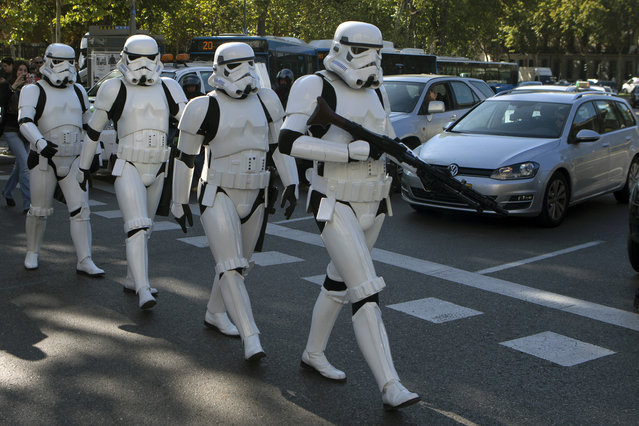 Star Wars Storm Trooper characters cross the street after a giant Star Wars helmet was unveiled, during the inauguration of an open air exhibition called 'Face the Force' in Madrid, Spain, Friday, October 30, 2015. Seven other giant helmets are due to be placed in various corners in the city. (Photo by Paul White/AP Photo)