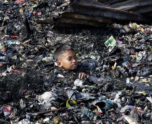A boy sifts through the debris Wednesday, December 10, 2014 following an overnight fire at an informal settlers' community of Tonsuya in Malabon city, north of Manila, Philippines. The fire razed more than 200 houses and affected close to a thousand people. Fire officials said five people were injured and currently investigating its cause. (Photo by Bullit Marquez/AP Photo)