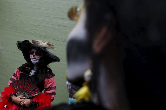 "A woman with her face painted to look like the popular Mexican figure called ""Catrina"", looks on as she takes part in the annual Catrina Fest in Mexico City November 1, 2015. (Photo by Carlos Jasso/Reuters)"