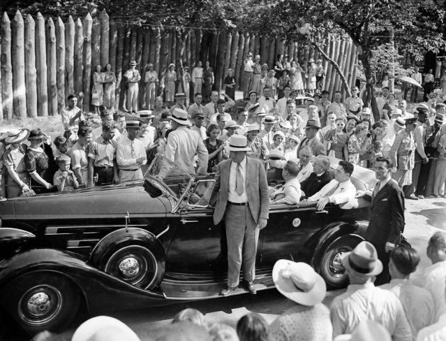 """With stockades of the reconstructed old Fort Raleigh in the background, President Franklin D. Roosevelt arrives for his address on the """"lost colony"""", August 18, 1937. Next to him in the back seat of the auto is Gov. Clyde R. Hoey of North Carolina and next to him, closest to camera, is Rep. Lindsay C. Warren (D-N.C.). (Photo by eorge R. Skadding/AP Photo)"""