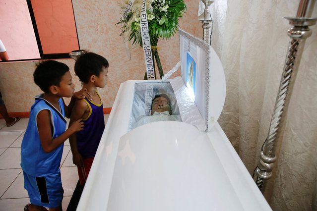 Children look inside a coffin with a man whose body was found earlier this week with a placard accusing him of being a drug pusher, in a community centre where relatives and friends gathered to mourn his death in Manila, Philippines October 8, 2016. (Photo by Damir Sagolj/Reuters)
