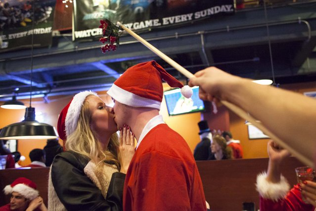 "Santarchy participants Morgan Whitney (L) and Alec Thomas (R) share an impromptu kiss under a ""mistletoe stick"" held by another Santarchy participant at Gameworks in Seattle, Washington December 13, 2014. (Photo by David Ryder/Reuters)"