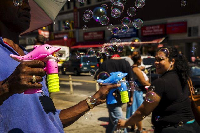 A street vendor blows bubbles on the street in a region of the South Bronx that has seen a deadly outbreak of Legionnaires' disease in New York August 7, 2015. (Photo by Lucas Jackson/Reuters)
