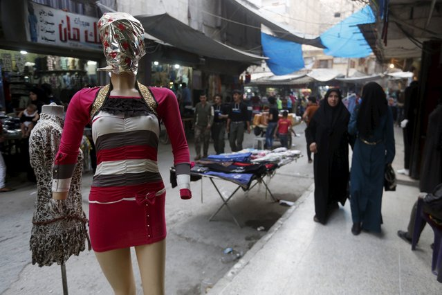 Women walk past a mannequin with a covered face as they shop ahead of the Muslim festival of Eid-al-Adha in Aleppo, Syria September 23, 2015. (Photo by Hamid Khatib/Reuters)