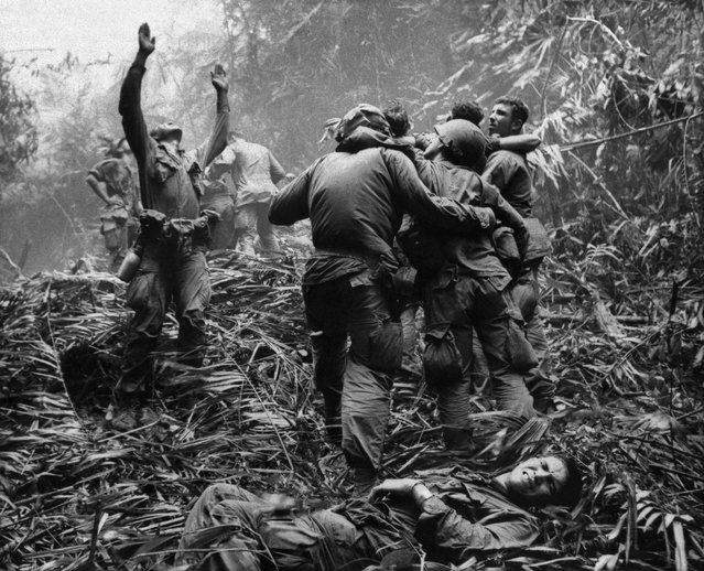 This April 1968 file photo shows the first sergeant of A Company, 101st Airborne Division, guiding a medevac helicopter through the jungle foliage to pick up casualties suffered during a five-day patrol near Hue, April 1968. Two soldiers in the photo, Dallas Brown, bottom, and Tim Wintenburg, far right, recently reunited to talk to The Associated Press about the iconic photo and the war. (Photo by Art Greenspon/AP Photo)
