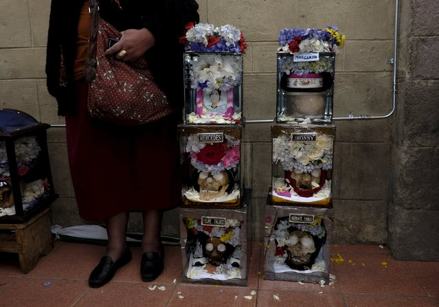 """A devotee stands near skulls placed on the floor during a ceremony held for the """"Dia de las natitas"""" (Day of the Skull) celebrations at the General Cemetery of La Paz November 8, 2015. (Photo by David Mercado/Reuters)"""