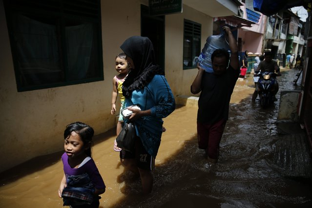 A family walks through a flooded alley as they evacuate from their house at Kampung Melayu residential area in Jakarta, December 23, 2014. Torrential rains that have continued in Indonesia in recent days have widened the number of flooded areas that include Jakarta and Bandung, a local newspaper said on Tuesday. (Photo by Reuters/Beawiharta)