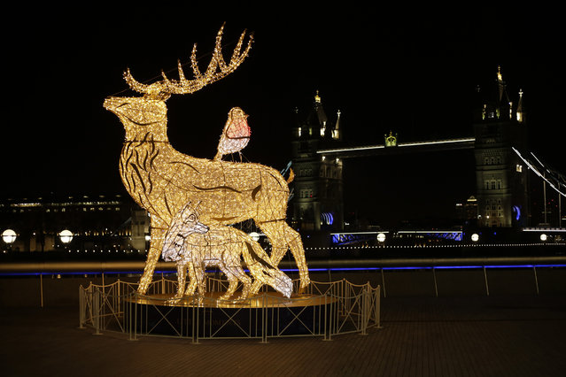 A Christmas lights sculpture stands backdropped by Tower Bridge, during England's second coronavirus lockdown, Thursday, November 26, 2020. The visual effects in blue and white are to thank National Health Service (NHS) and key workers for all they did during this year's coronavirus outbreak. (Photo by Matt Dunham/AP Photo)