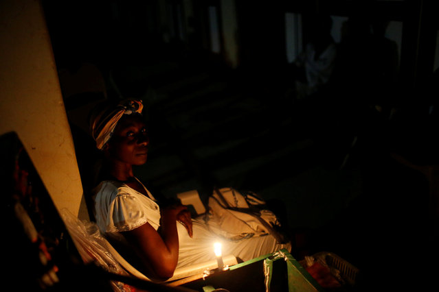 A woman sits beside a candle after Hurricane Matthew hit Jeremie, Haiti, October 14, 2016. (Photo by Carlos Garcia Rawlins/Reuters)