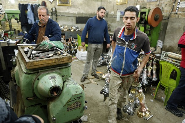 Workers are pictured at a shisha manufacturing factory in Baghdad December 17, 2014. (Photo by Thaier Al-Sudani/Reuters)