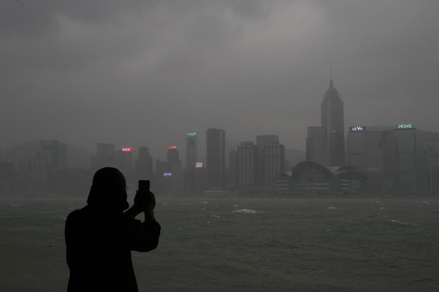 A woman takes pictures on the waterfront of Victoria Harbour as Typhoon Haima approaches Hong Kong, Friday, October 21, 2016. (Photo by Vincent Yu/AP Photo)