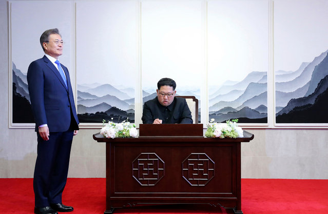 North Korean leader Kim Jong Un signs a guest book next to South Korean President Moon Jae-in, left, inside the Peace House at at the border village of Panmunjom in Demilitarized Zone Friday, April 27, 2018. (Photo by Korea Summit Press Pool via AP Photo)