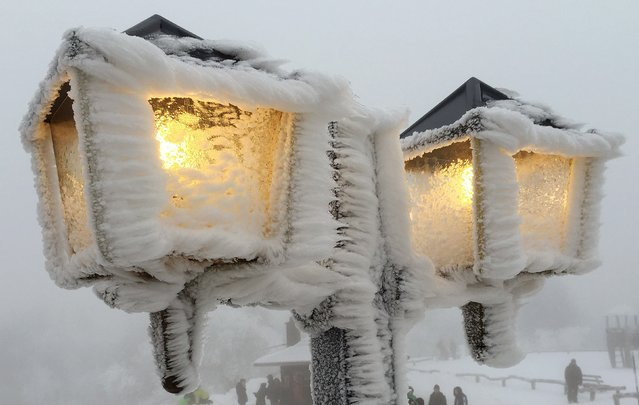 Streetlamps are covered in snow and ice outside a restaurant on the peak of the Feldberg mountain, 20km (12.4 miles) outside of Frankfurt, December 31, 2014. (Photo by Kai Pfaffenbach/Reuters)