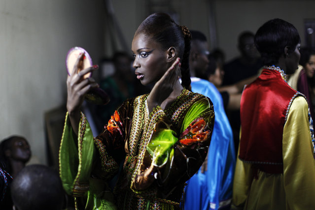 A model wearing a creation by Moroccan designer Siham Kharbough fixes her makeup backstage during Dakar Fashion Week July 15, 2010. (Photo by Finbarr O'Reilly/Reuters)