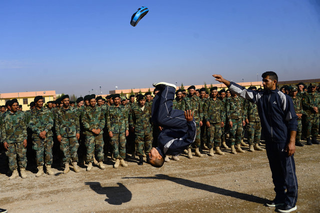 An Afghan National Army (ANA) soldier demonstrates his skills during a graduation a ceremony in a military base in the Guzara district of Herat province on December 2, 2020. (Photo by Hoshang Hashimi/AFP Photo)