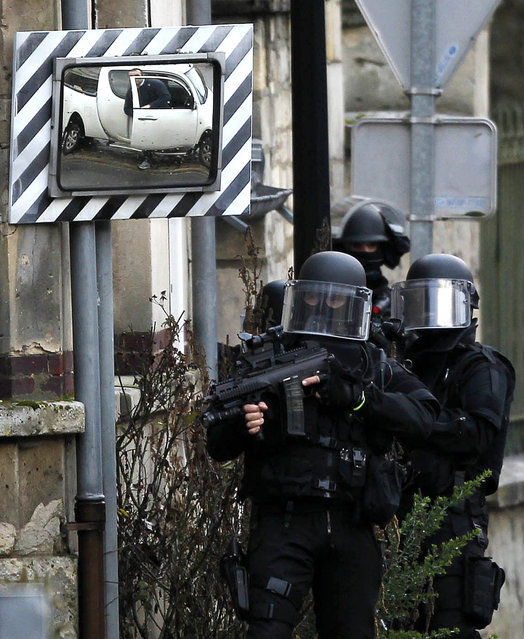 SWAT police officers patrol in the village of Longpont, northeast of Paris, in search of the two heavily armed brothers suspected in the massacre at Charlie Hebdo newspaper, Thursday, January 8, 2015. Scattered gunfire and explosions shook France on Thursday as its frightened yet defiant citizens held a day of mourning for 12 people slain at a Paris newspaper. (Photo by Michel Spingler/AP Photo)