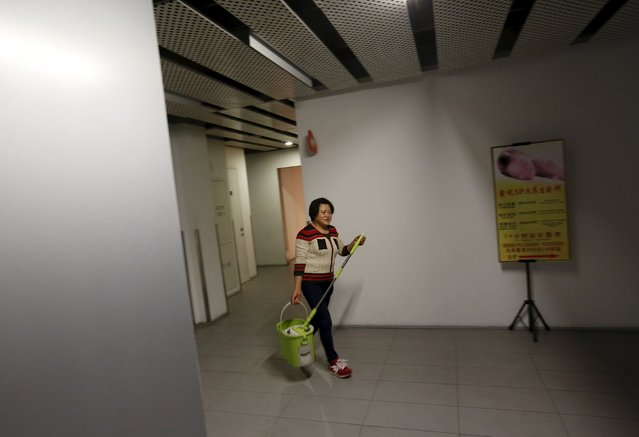"""Migrant worker Lai Yongmei, 47, starts work as a cleaner in downtown Beijing, China, November 16, 2015. Yongmei commutes 90 minutes from her village home in the Shunyi district. Yongmei said, """"I moved to a village near the airport around 6 years ago. Many people from my hometown live in this village. My husband and I share a room. It's 700 yuan a month. And for winter, we'll need to pay 300 extra for heating"""". (Photo by Kim Kyung-Hoon/Reuters)"""