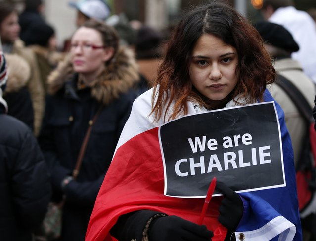 """A woman wearing a French national flag holds a """"We are Charlie"""" sign during a march for the victims of the shootings by gunmen at the offices of the satirical weekly newspaper Charlie Hebdo in Paris, in Liverpool, northern England January 11, 2015. (Photo by Phil Noble/Reuters)"""