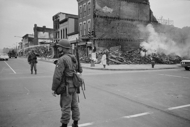 A soldier standing guard at 7th and N Street, N.W., Washington, D.C., with the ruins of buildings that were destroyed during the riots that followed the assassination of Martin Luther King, Jr., April 8, 1968. (Photo by Reuters/Library of Congress)