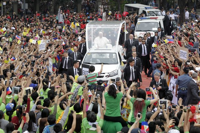 Pope Francis waves to pilgrims during a meeting with youths at the University of  Santo Tomas (UST) in Manila January 18, 2015. (Photo by Romeo Ranoco/Reuters)