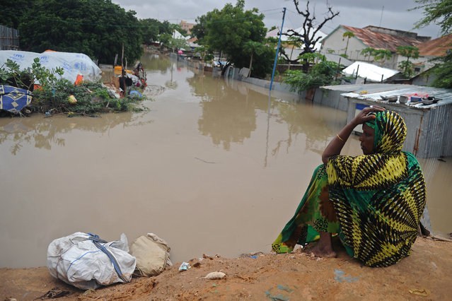 A woman living at a camp for the internally displaced sits on high ground above a flooded street on May 20, 2018 in Mogadishu after temporary shelters were inundated in Somalia's capital following heavy overnight rainfall. (Photo by Mohamed Abdiwahab/AFP Photo)
