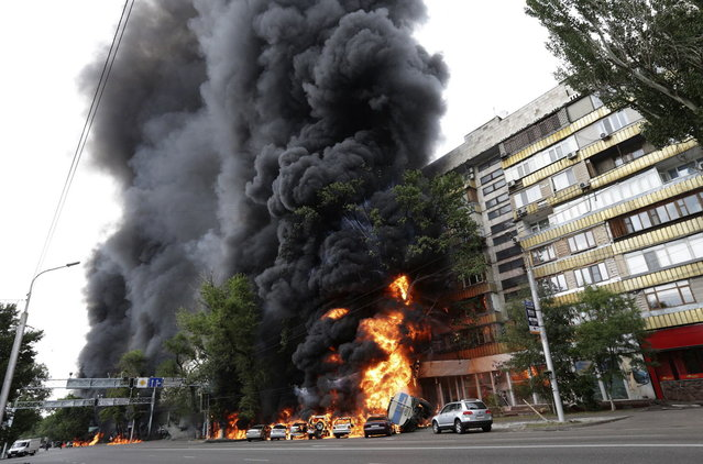Burning vehicles are seen at the site of a fire in Almaty June 27, 2013. A 16-ton tank truck rolled over after an accident, setting parked cars and a nearby apartment building ablaze, Emergency Ministry reported. (Photo by Sergey Khodanov/Reuters)