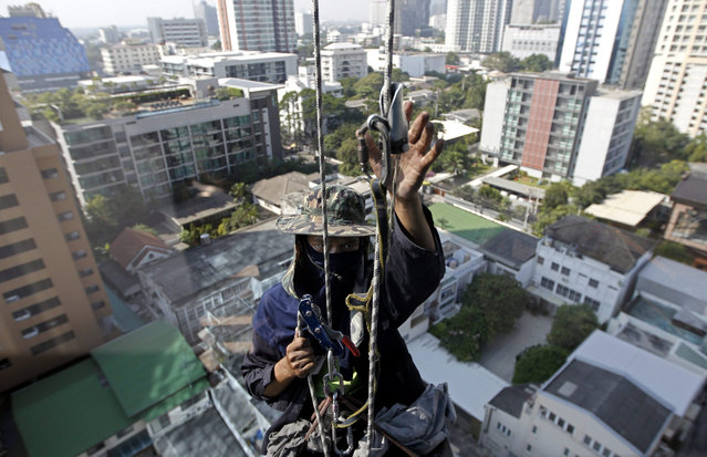 A picture taken through a window glass shows a window cleaner working on a high rise office building in central Bangkok, Thailand, 10 December 2015. Thailand's gross domestic product grew 2.9 percent in the third quarter of 2015, the highest growth in three years showing sign of fast economic recovery as a result of the consumers and industrial confidence indexes are picking up due to the government stimulus measures and the increasing of tourist arrivals which aimed to reach over 30 million while the Thai economy in 2016 is forecasted to expand by three to four percent, according to the National Economic and Social Development Board. (Photo by Rungroj Yongrit/EPA)