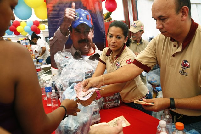 People buy goods in a Mega-Mercal, a subsidized state-run street market, in Caracas January 24, 2015. (Photo by Carlos Garcia Rawlins/Reuters)