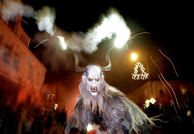 A man dressed as a devil performs during a Krampus show in the southern Bohemian town of Kaplice, December 12, 2015. Each year people in traditional costumes and masks parade through the streets to perform an old ritual to disperse the ghosts of winter. (Photo by David W. Cerny/Reuters)