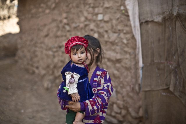An Afghan refugee girl holds her younger sister in a slum on the outskirts of Islamabad, Pakistan, Sunday, January 18, 2015. (Photo by Muhammed Muheisen/AP Photo)