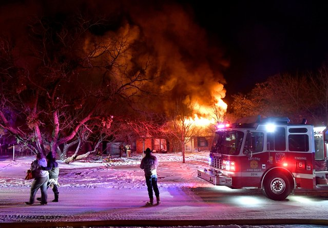 Residents of Cedar Crest Drive walk past their burning house as firefighters, who were only able to draw water from one hydrant because all three city water treatment plants were offline due to cold weather power outages, try to contain the fire in Abilene, Texas, February 15, 2021. The house could not be saved due to the low water pressure. (Photo by Ronald W. Erdrich/Reporter-News/USA Today Network via Reuters)