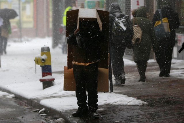 A man stands with a box over his head as it snows in the Queens borough of New York January 26, 2015. (Photo by Shannon Stapleton/Reuters)