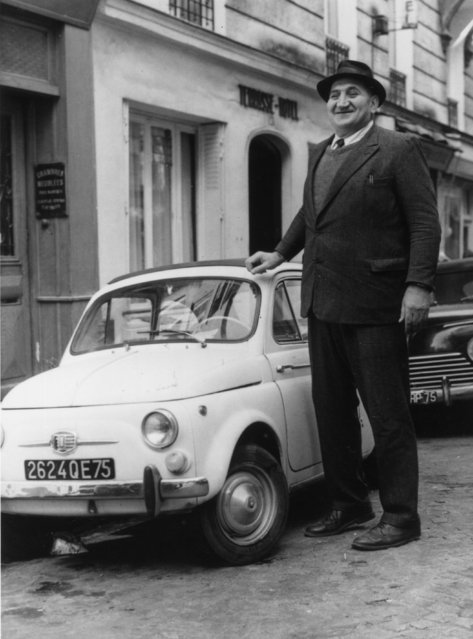 Assen Ivanov Giorgiev, a Bulgarian who weighs 256 kilos with a height of 2.8 metres, poses next to a car far too small for him. He started a career as a boxer and wrestler, but can no longer find an opponent willing to challenge him. 22nd September 1965. (Photo by Keystone/Getty Images)