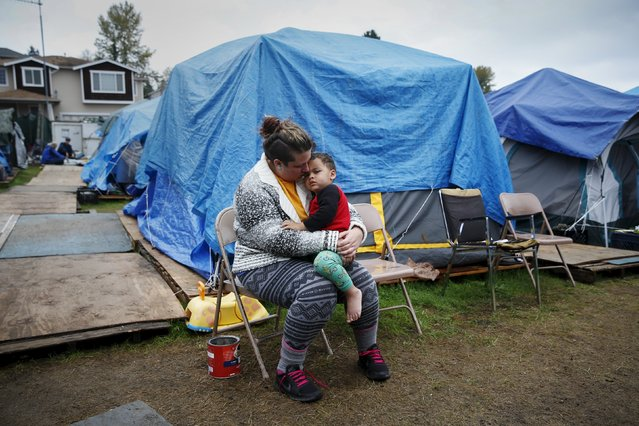 "Kadee Ingram, 28, holds her son Sean, 2, at SHARE/WHEEL Tent City 3 outside Seattle, Washington October 13, 2015. Ingram lost her job, and soon afterwards her partner Renee lost her job. ""It got (to) the point where we couldn't get a job fast enough and we lost our apartment"", Ingram said. ""Coming here, we really like it, being outside especially, we feel safe. We wish we would have known about it sooner"". (Photo by Shannon Stapleton/Reuters)"