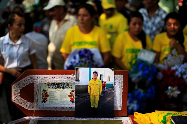 A photograph of 14-year-old Comandos de Salvamento volunteer Erick Beltran, who was killed by suspected gang members, is seen during his funeral in Quezaltepeque, El Salvador April 13, 2016. Beltran is the first volunteer to be killed on duty in 56 years of CDS. (Photo by Jose Cabezas/Reuters)