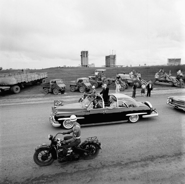 President Eisenhower stands in the back of car and waves as he rides past building under construction in Brasilia, new capitol city of Brazil, February 23, 1960 for his welcoming reception. Workers manning construction vehicles pause in their tasks to wave in return. (Photo by AP Photo)