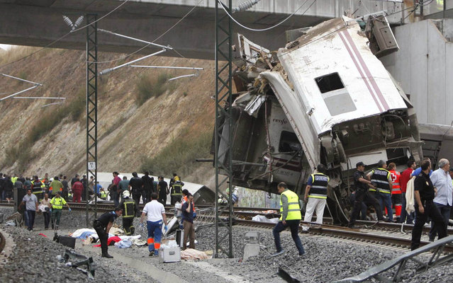 Emergency personnel respond to the scene of a train derailment in Santiago de Compostela, Spain, on Wednesday, July 24, 2013. A train derailed in northwestern Spain on Wednesday night, toppling passenger cars on their sides and leaving at least one torn open as smoke rose into the air. Dozens were feared dead, with possibly even more injured. (Photo by Antonio Hernandez/AP Photo/El correo Gallego)