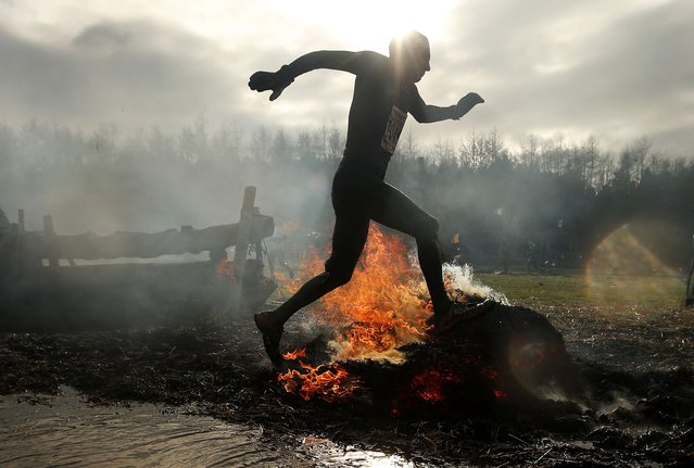 A competitor runs through flames during the Tough Guy event in Perton, central England, February 1, 2015. (Photo by Phil Noble/Reuters)
