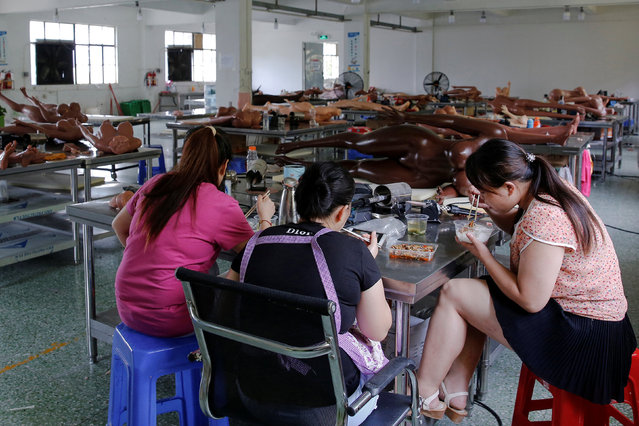 Workers have lunch among s*x dolls at the WMDOLL factory in Zhongshan, Guangdong Province, China, July 12, 2018. The factory has over 200 full-time workers, all dolls are handmade and each requires the cooperation of over five workers. (Photo by Aly Song/Reuters)