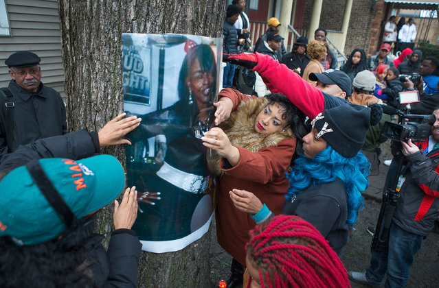 The daughters of Bettie Jones, along with friends and supporters, hang a picture of her during a vigil outside the family home on December 27, 2015 in Chicago, Illinois. Bettie Jones was shot and killed yesterday at the front door of her home by police responding to a domestic dispute call made by her upstairs neighbor. Quintonio LeGrier, was also killed by police during the incident. (Photo by Scott Olson/Getty Images)