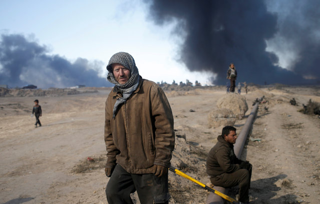 Men stand in front of oilfields burned by Islamic State fighters in Qayyara, south of Mosul, Iraq November 23, 2016. (Photo by Goran Tomasevic/Reuters)