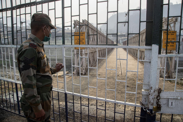 An Indian paramilitary soldier stands guard near the bridge on Tiau river along the India-Myanmar border in Mizoram, India, Saturday, March 20, 2021. Several Myanmar police officers who fled to India after defying army orders to shoot opponents of last month's coup are urging Prime Minister Narendra Modi's government to not repatriate them and provide them political asylum on humanitarian grounds. (Photo by Anupam Nath/AP Photo)