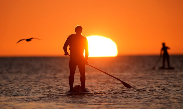 Paddleboarders at sunrise in Cullercoats Bay, North Tyneside, on the North East coast of England on Saturday, February 27, 2021. (Photo by Owen Humphreys/PA Images via Getty Images)