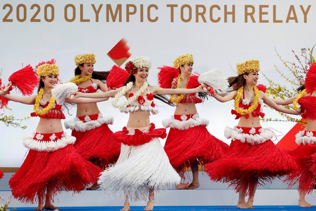 """Members of the Spa Resort Hawaiians Dancing Team """"Hula Girls"""" perform during an opening ceremony on the first day of the Tokyo 2020 Olympic torch relay in Naraha, Fukushima prefecture on March 25, 2021. (Photo by Kim Kyung-Hoon/Pool via AFP Photo)"""