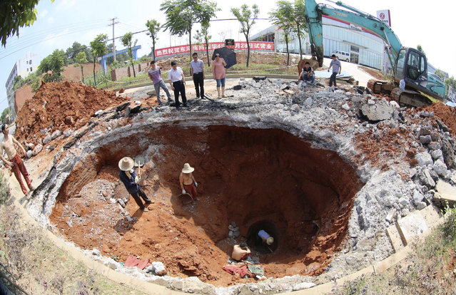 A rescue team works under a caved-in area on a road in Loudi, Hunan province, June 18, 2013. The road surface sank after a truck drove past. A motorcyclist riding behind the truck was injured, according to local reports. (Photo by Reuters/China Daily)