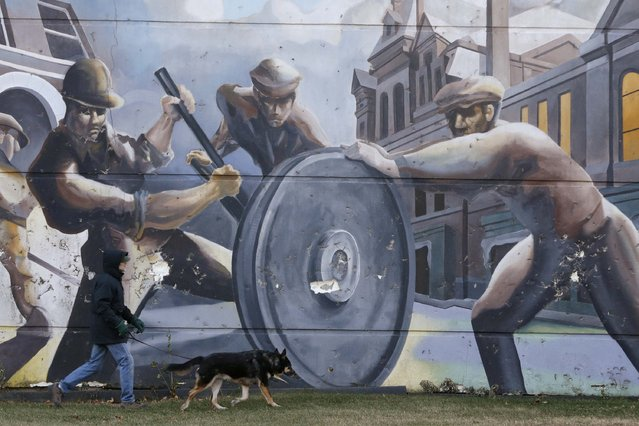 A man walks his dog past a mural depicting factory workers in the historic Pullman neighborhood in Chicago November 20, 2014. U.S. President Barack Obama is expected to announce the designation of the Pullman neighborhood as a national park on February 19, according to park advocates. (Photo by Andrew Nelles/Reuters)