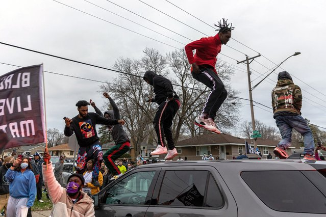Protesters stand on top of a police car as they clash after an officer shot and killed a black man in Brooklyn Center, Minneapolis, Minnesota on April 11,2021. Protests broke out April 11, 2021 night after US police fatally shot a young Black man in a suburb of Minneapolis – where a former police officer is currently on trial for the murder of George Floyd. Hundreds of people gathered outside the police station in Brooklyn Center, northwest of Minneapolis. Police fired teargas and flash bangs at the demonstrators, according to an AFP videojournalist at the scene. (Photo by Kerem Yucel/AFP Photo)