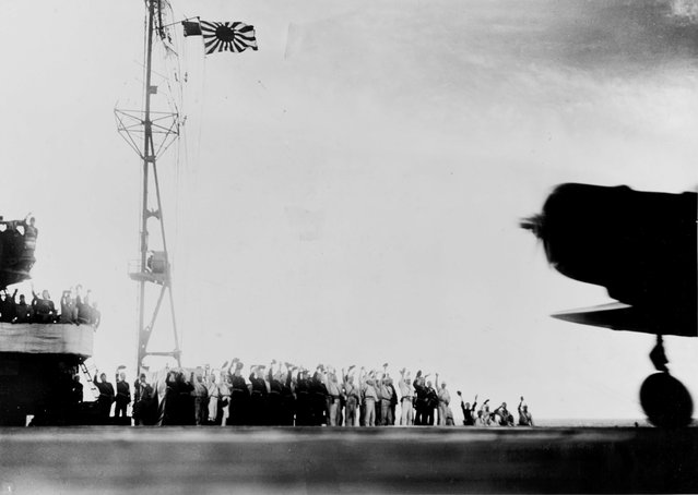 The crew of the Japanese carrier Shokaku cry Banzai as a Type 97 Kate carrier attack plane takes off as the second wave attack is launched on Pearl Harbor, Hawaii, U.S. December 7, 1941. (Photo by Reuters/U.S. Navy/National Archives)
