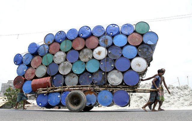 Bangladeshi labourers pull a cart of used containers to the market in Dhaka April 26, 2007. (Photo by Rafiqur Rahman/Reuters)