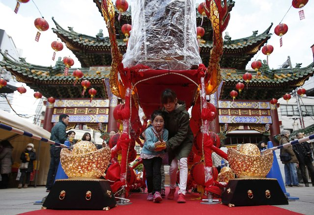 A girl and her mother walk through a Chinese portable shrine during the Chinese Lunar New Year at Chinatown in Yokohama, south of Tokyo February 19, 2015. (Photo by Yuya Shino/Reuters)
